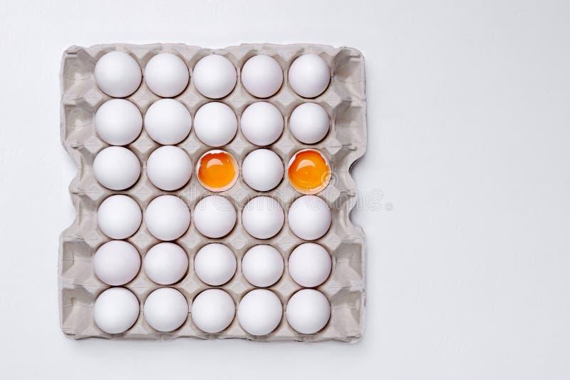 Ägg i pappers- magasin med två knäckte öppet på den vita backgrouen arkivbild