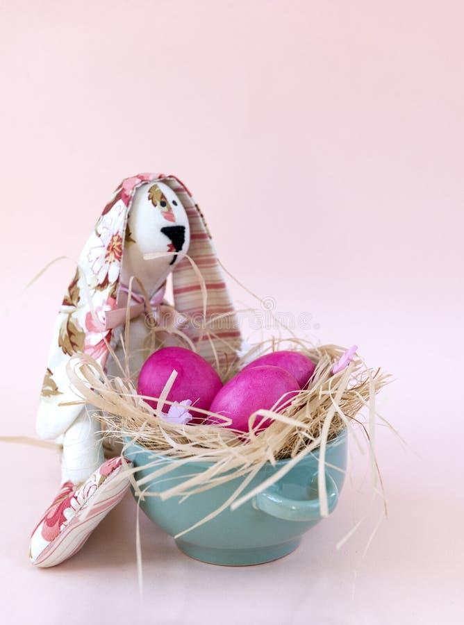 3 ägg, kanin, rosa påskägg, rede, fega kokta ägg royaltyfria foton