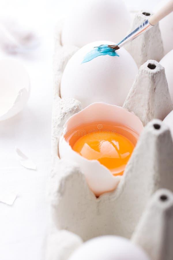 Ägg med äggula i en papp för påsk som dekorerar ägget med blått, färgar royaltyfri foto