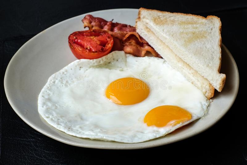 Ägg med bacon och bröd för frukost arkivfoto