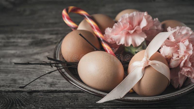 Ägg med bandet, filialer, blommor och godisen på den horisontalträtabellen royaltyfri bild