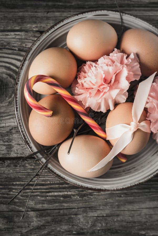 Ägg med bandet, filialer, blommor och godisen på trätabelllodlinjen royaltyfri bild