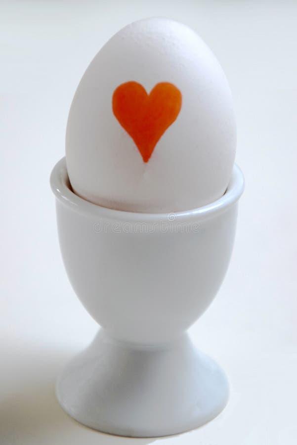 Ägg med en röd hjärta arkivfoton