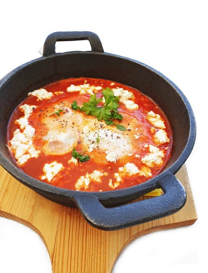 Ägg med ny tomater och fetaost kallade saganakien - grekisk kokkonst arkivfoto
