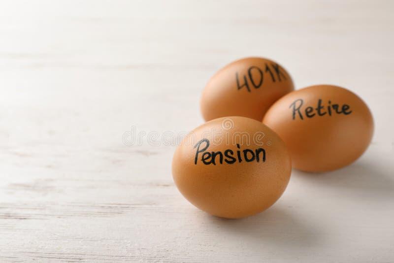 Ägg med ord PENSION, RETRÄTTSIGNAL och 401k på träbakgrund arkivfoto