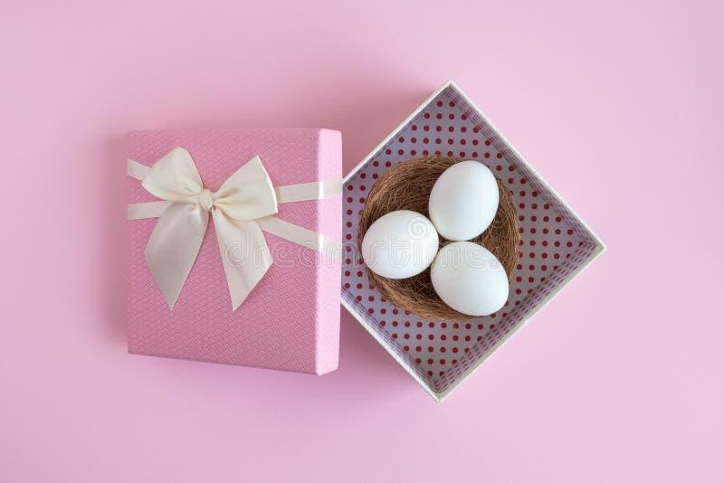Ägg med redet i rosa för easter för gåvaask abstrakt begrepp ferie royaltyfri fotografi