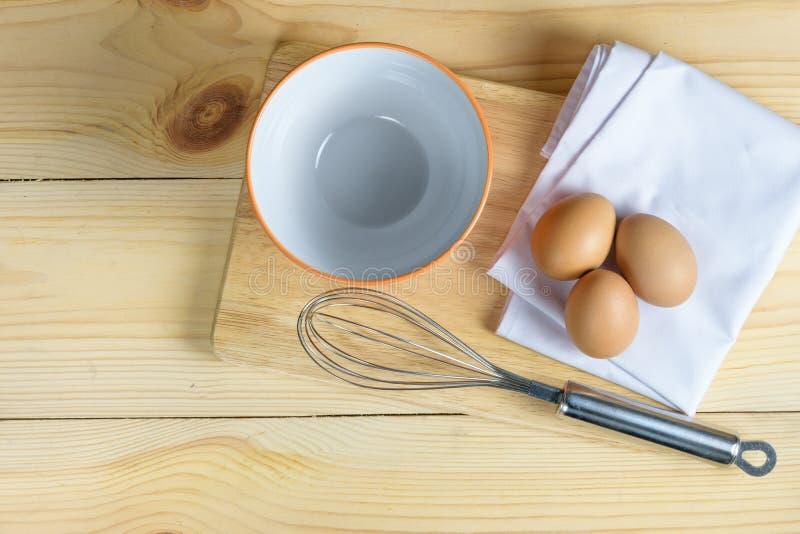 Ägg med viftar och tömmer den orange bunken på träplattan royaltyfri fotografi