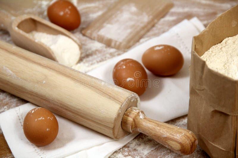 Ägg, mjöl och kavel på en trätabell arkivbilder