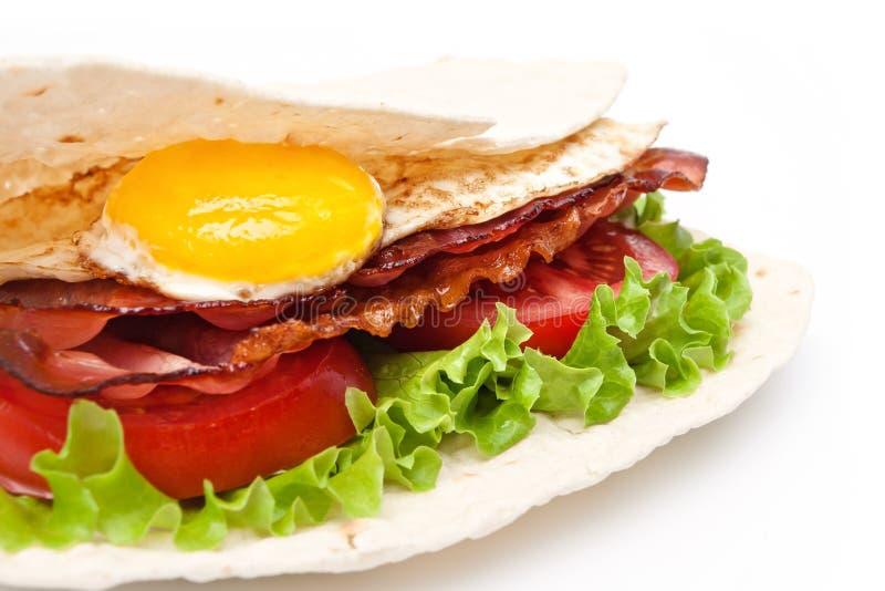 Ägg och bacon som räknas in i pannkakan royaltyfria foton