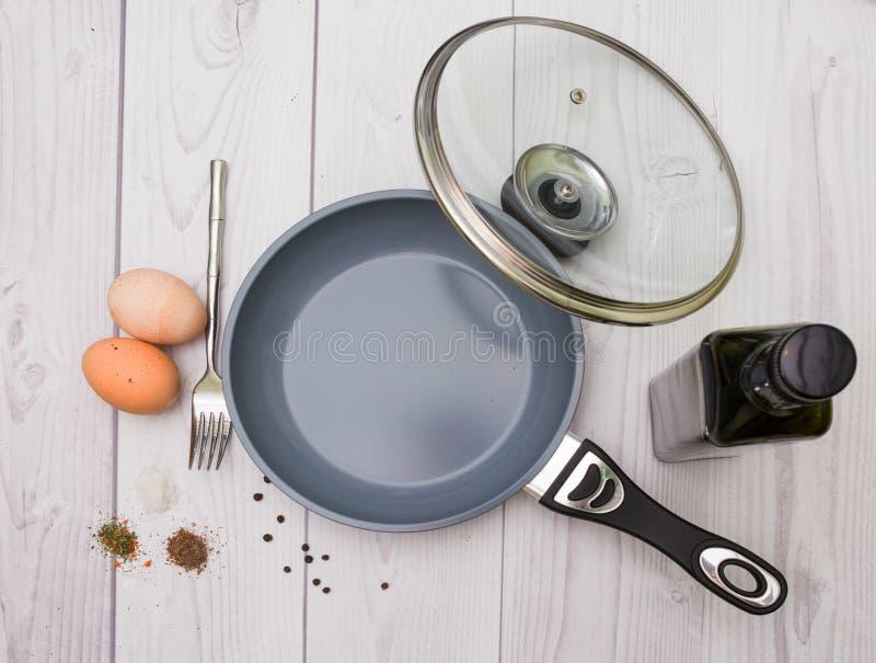 Ägg olja, panna, kryddor, gaffel arkivbilder