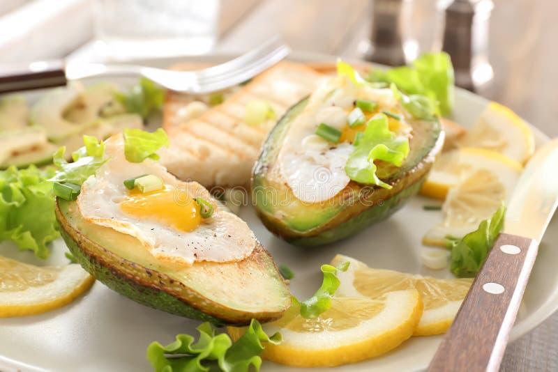 Ägg som bakas i avokado och skivor av rostat bröd på plattan, closeup arkivfoton