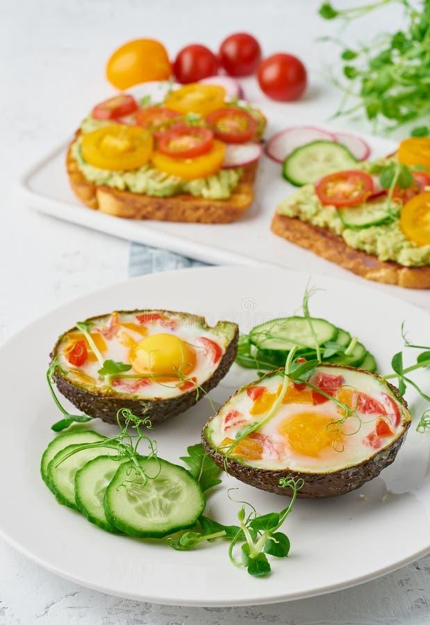 Ägg som bakas i avokadot, rostat bröd, frukost, closeup royaltyfri bild