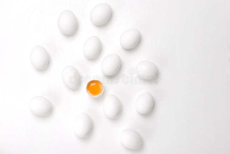 Ägg Sprucken en och grupp av hela ohörda ägg på en vit bac royaltyfria foton