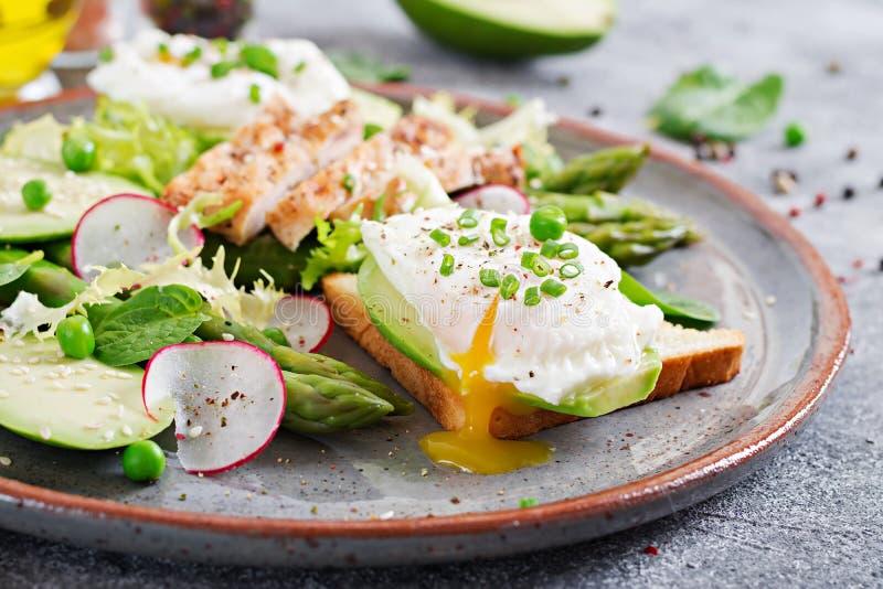 Ägg tjuvjagade på rostat bröd med den avokado-, sparris- och hönafilén på galler arkivbild