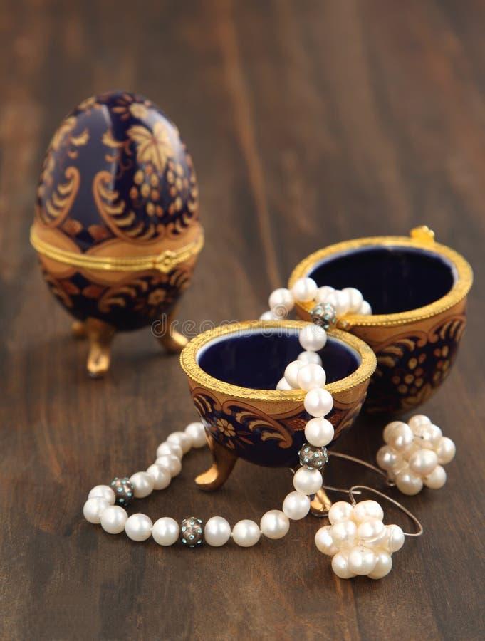 Ägget formade casketen med ett pärlemorfärg halsband och örhängen arkivbilder