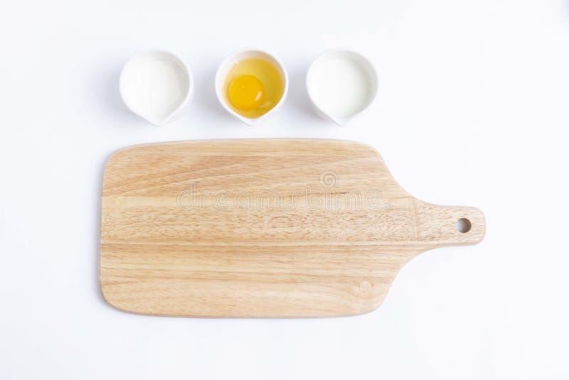 Ägget mjöl, mjölkar, skärbrädan fotografering för bildbyråer