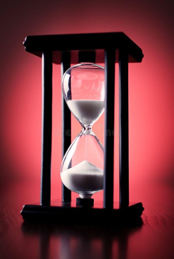 Äggklocka eller timglas på en röd bakgrund royaltyfri bild