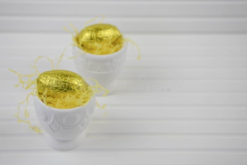Äggkoppar med guld- ägg för färgchokladpåsk på vit royaltyfri bild
