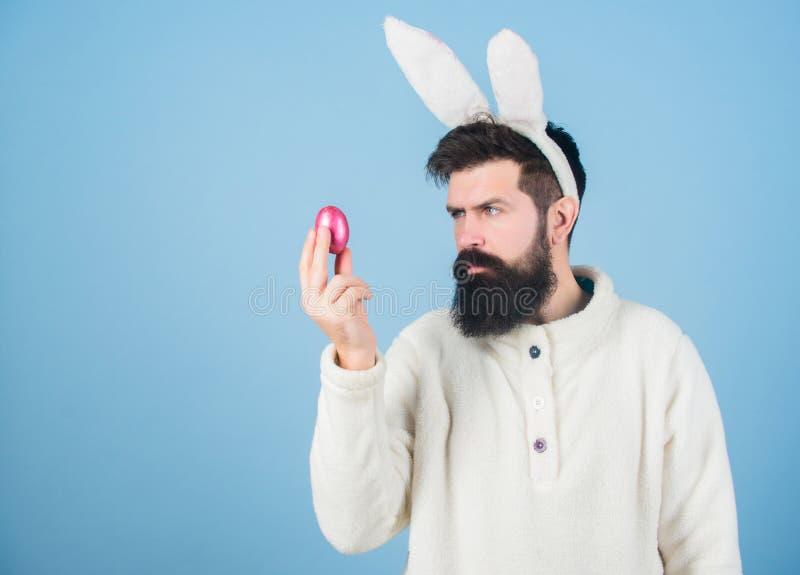 Äggrullning Skäggig man i påskkanindräkten som ser det kulöra ägget Hipster i långa kaninöron som rymmer påskägget arkivfoto