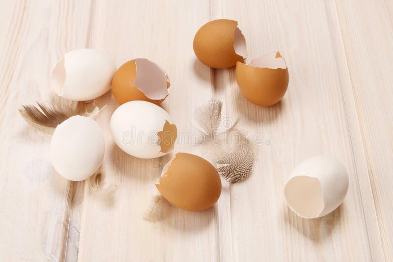 Äggskal på den vita trätabellen fotografering för bildbyråer