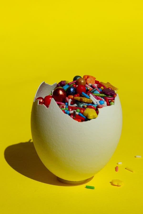 Äggskal som är full av färgrika godisar över gul bakgrund Abstrakt bakgrund för matingredienser royaltyfri bild