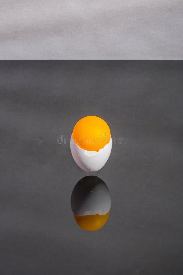 Äggskal som klibbas i luften ovanför tabellen med en orange boll royaltyfria foton