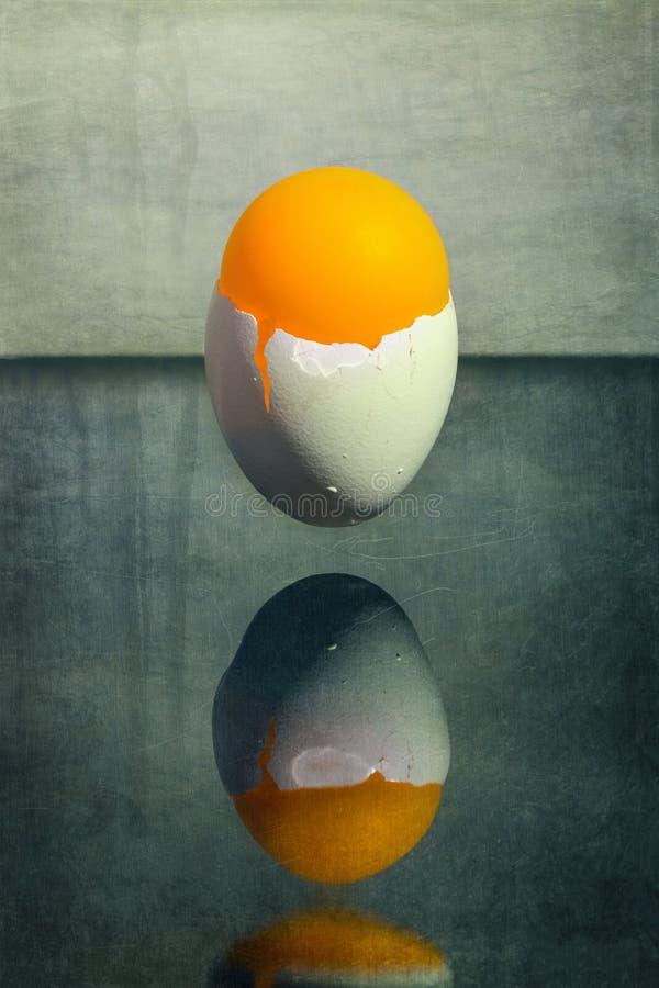 Äggskal som klibbas i luften ovanför tabellen med en orange boll, overklig stilleben arkivfoto