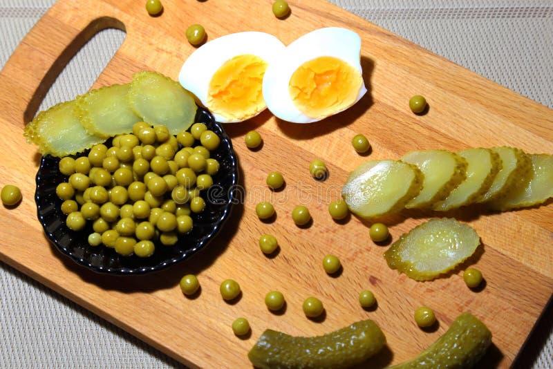 Äggula, inlagda ättiksgurkor och på burk gröna ärtor för att laga mat buller royaltyfri fotografi