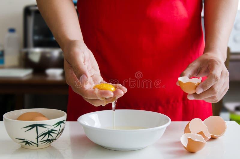 Äggula som är separat i handen för att laga mat arkivfoton