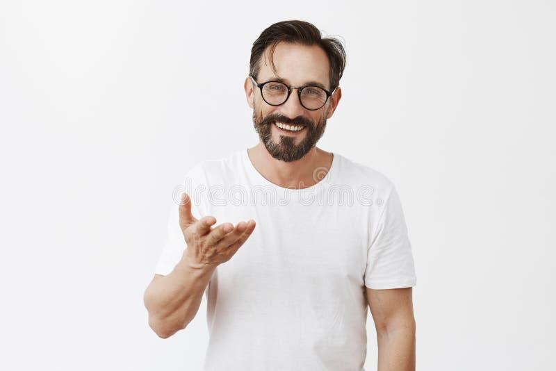 Ägna allt till dig Charmig tacksam europeisk man med skägget och stilfull frisyr i exponeringsglas som pekar med arkivfoto
