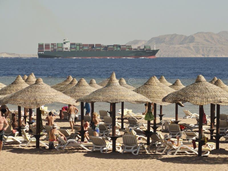 Ägypten, Sharm el-Sheikh: Erholungsortstrand mit mit Stroh gedeckten Regenschirmen und Sonnenbetten gegen den Hintergrund des Mee lizenzfreie stockfotos