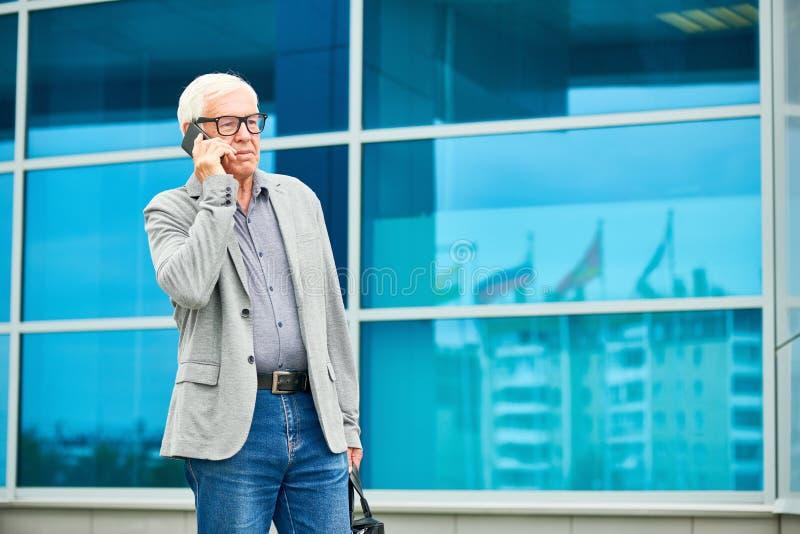Äldre affärsman som talar på smartphonen nära byggnad arkivbilder