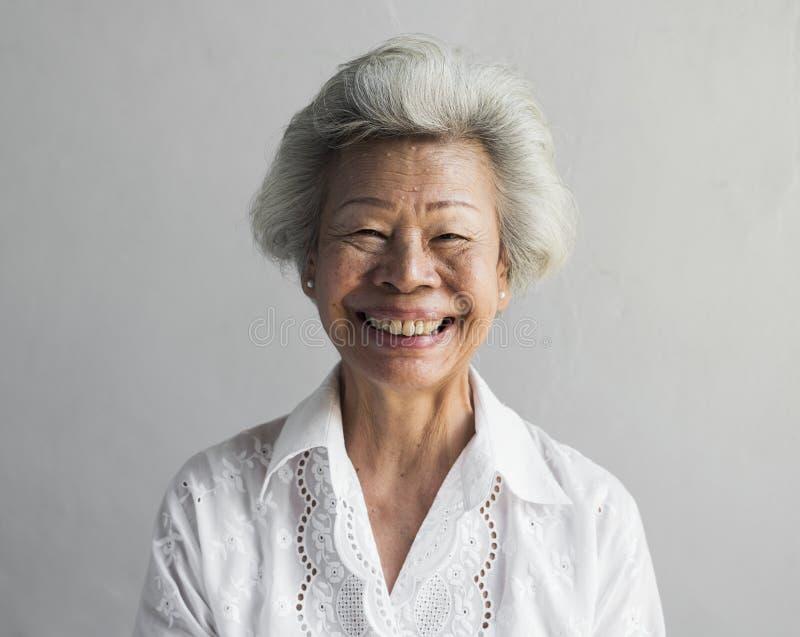 Äldre asiatisk kvinna som ler framsidauttrycksståenden arkivbilder