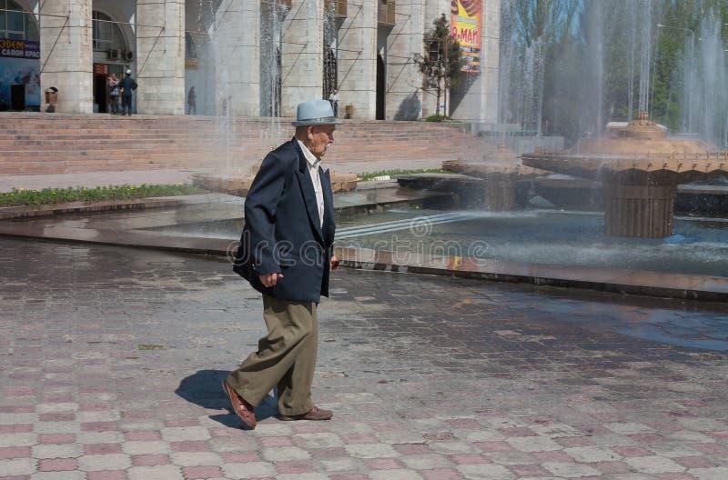 Äldre asiatisk man som går på alun-Förfyrkant royaltyfria bilder