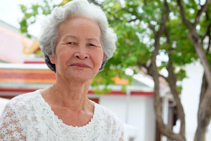 Äldre asiatiska kvinnor med gråaktigt hår har att le arkivfoto