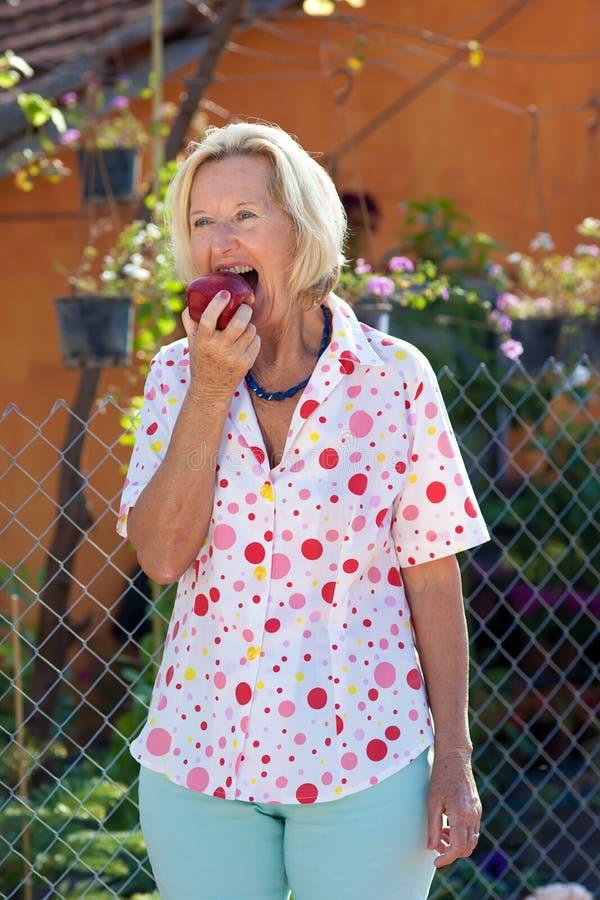 Äldre blond kvinna som äter ett nytt äpple royaltyfri fotografi