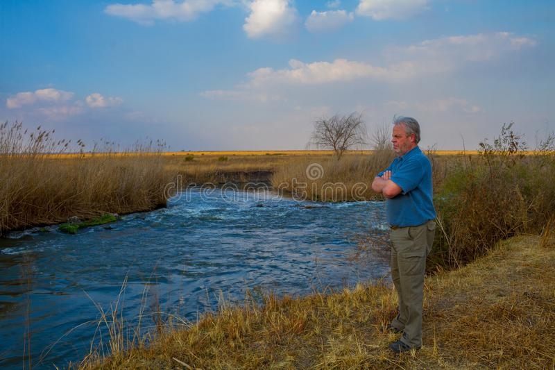 Äldre bonde som ser över en flod arkivfoton