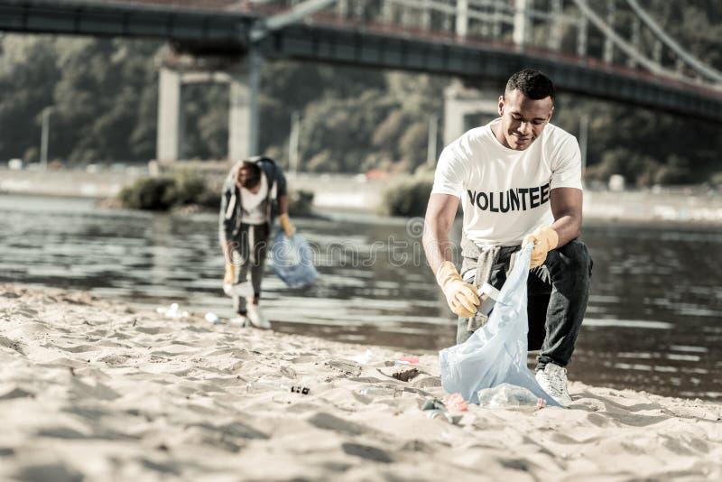 Äldre broder som sammanfogar hans sibling, medan arbeta som volontär på stranden arkivfoto