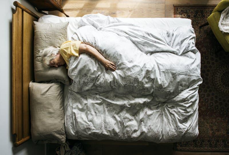 Äldre Caucasian kvinna som sover på sängen arkivbilder