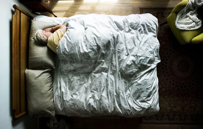 Äldre Caucasian kvinna som sover på sängen royaltyfri fotografi