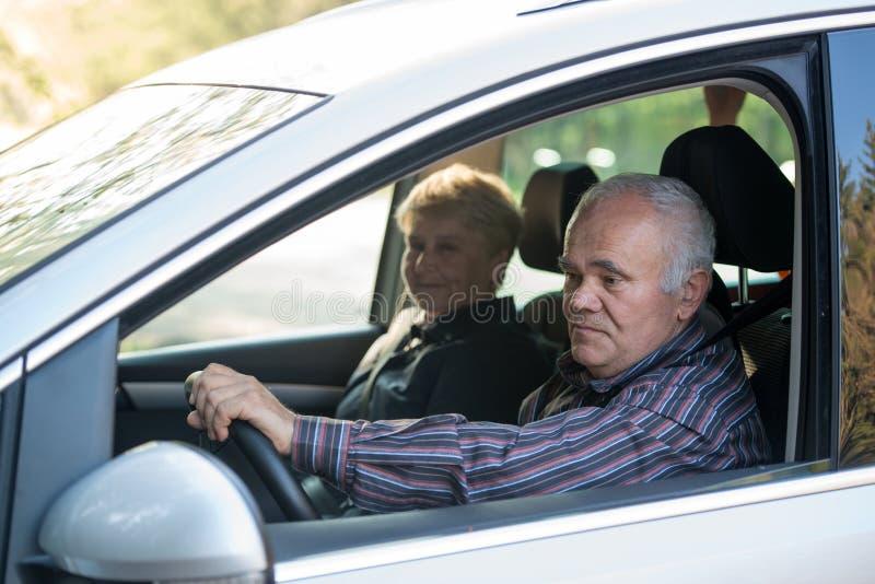 Äldre chaufför som använder smartphonen arkivbild