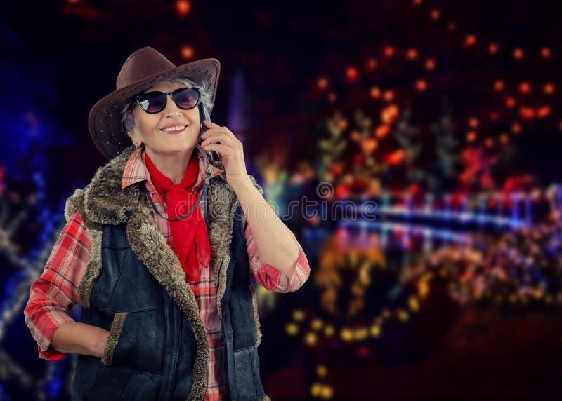 Äldre cowgirl som kallar på julbakgrund royaltyfri foto