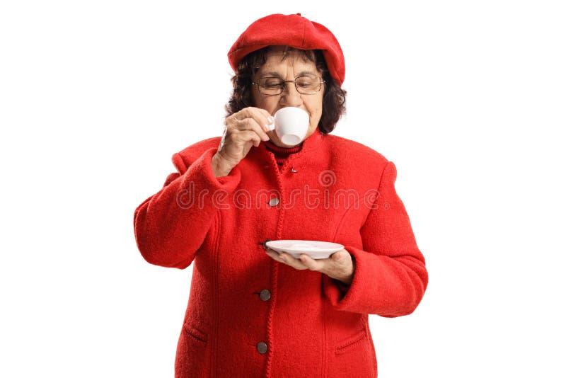 Äldre dam i ett rött lag som tar en smutt av espressokaffe royaltyfria foton