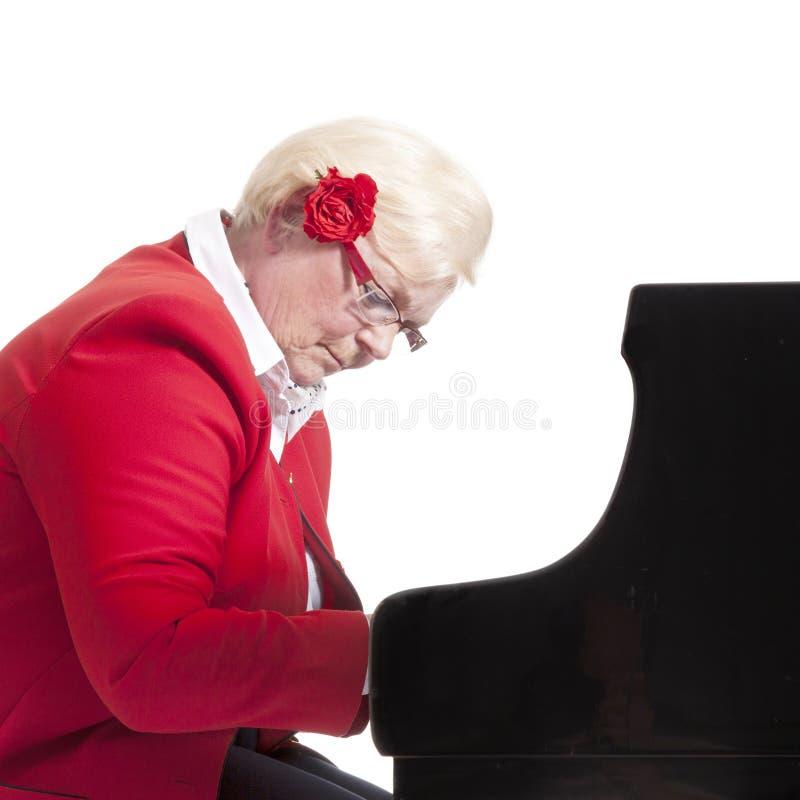 Äldre dam i rött spela flygeln royaltyfri bild