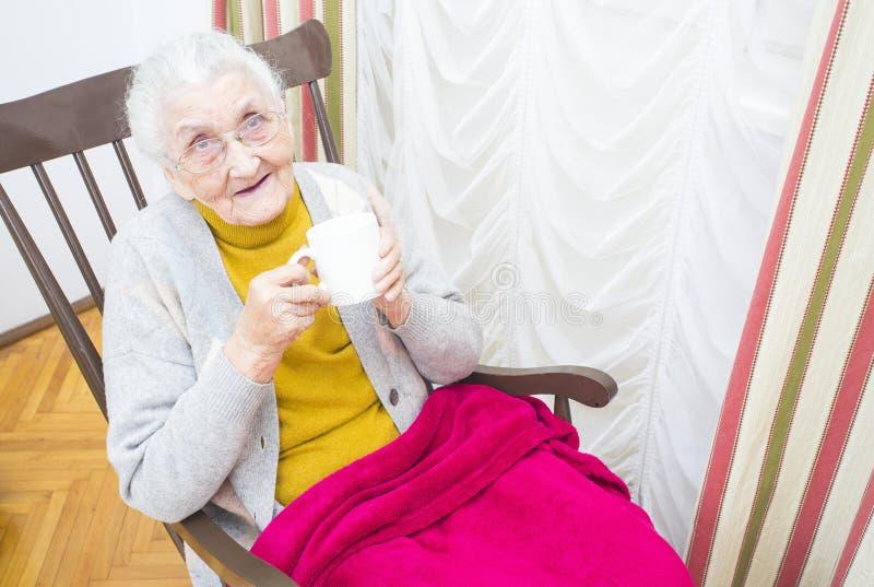 Äldre dam i stol fotografering för bildbyråer