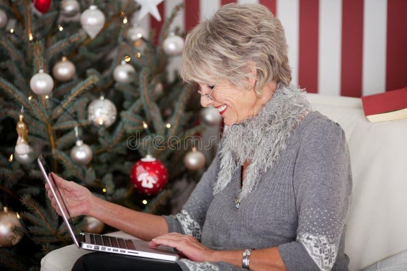 Äldre dam som överför julhälsningar royaltyfria bilder
