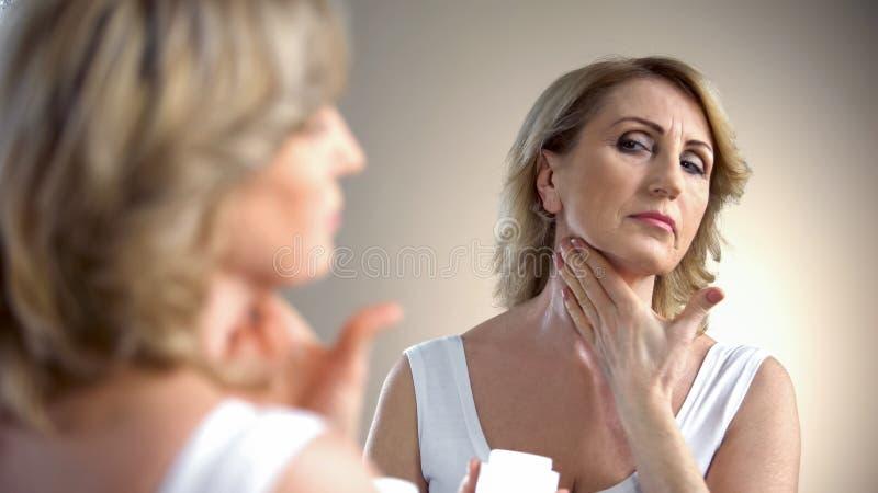 Äldre dam som applicerar anti--ålder kräm på halsen, hudomsorg i gamlingen, skrynklor royaltyfri foto