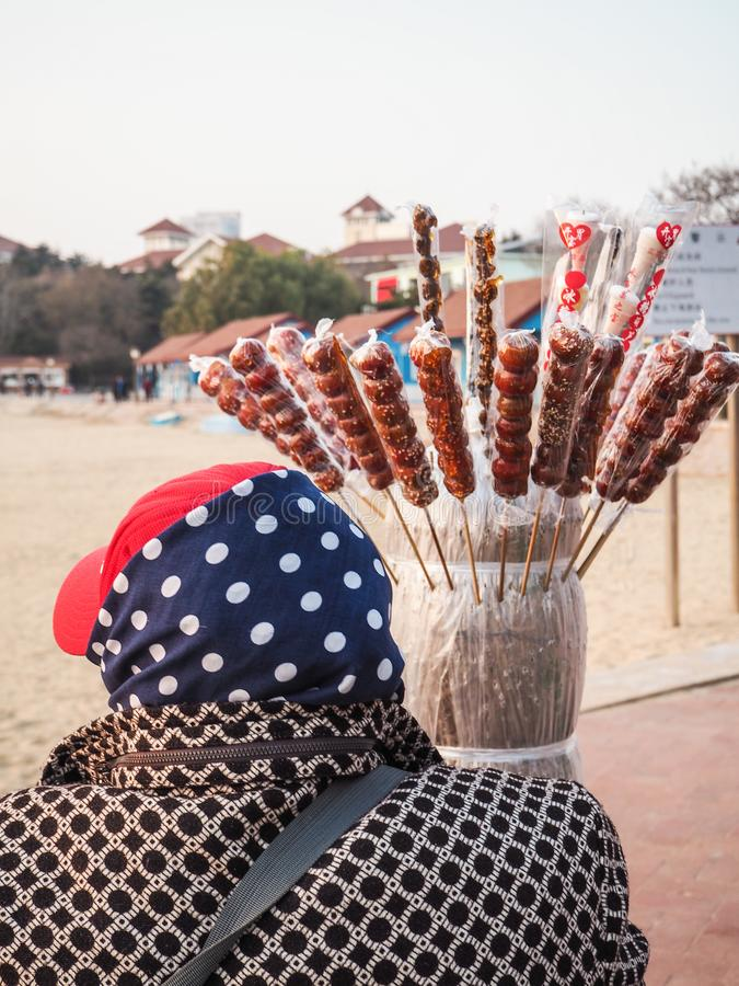 Äldre dam som säljer kanderad frukt på en pinne på en strand arkivfoton