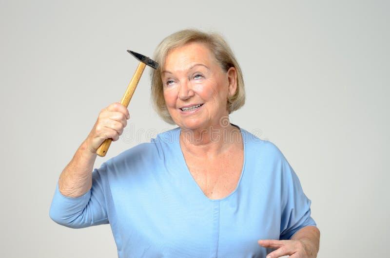 Äldre dam som slår hennes huvud med en hammare arkivbild