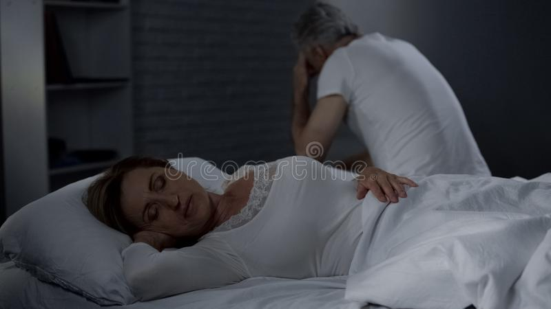 Äldre dam som sover, make som tillbaka sitter på den avlägsna kanten av säng, manhälsa royaltyfri fotografi